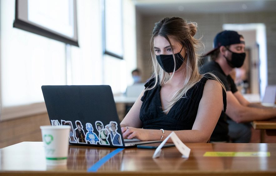 student wearing black face mask at table while using laptop