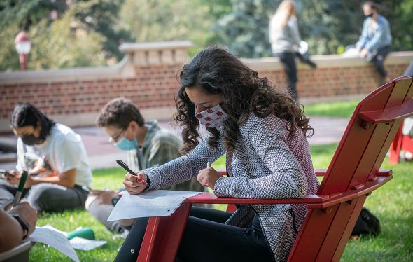 students sitting outside and writing