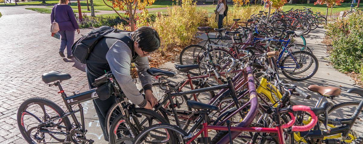 student at bike rack full of bikes