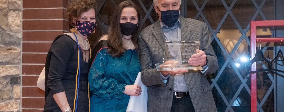students wearing a mask and accepting their diploma