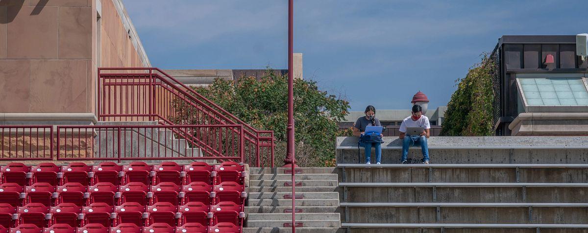 students using laptops sitting on stadium stairs