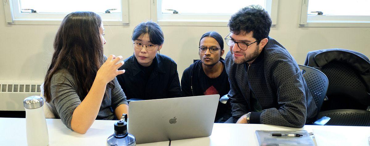 4 people gathered around laptop