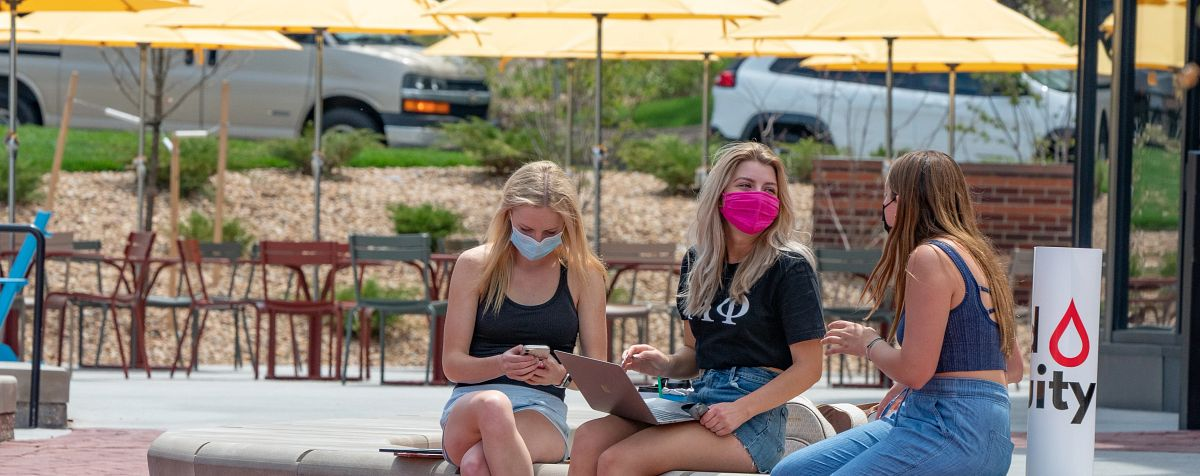 three female students outside sitting in common area wearing masks and talking