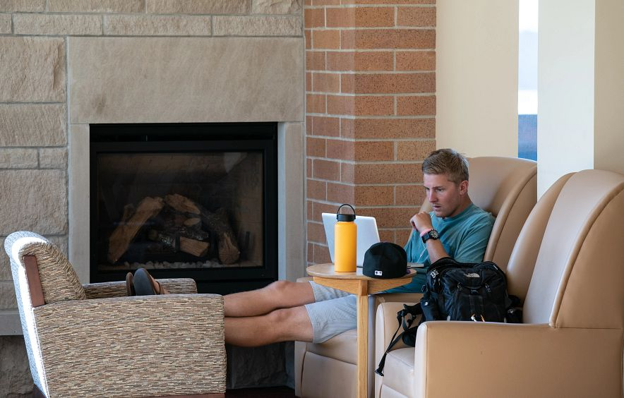 student seated on armchair by fireplace studying with laptop in DU campus building