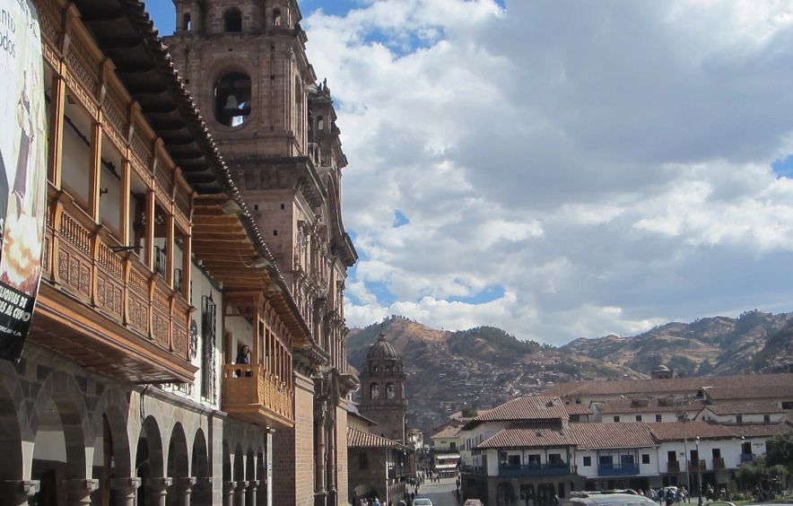 old style city buildings in front of mountains in background