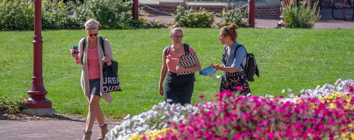 three students walking together on brick pathway with flowers in foreground