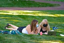 two students lying in the grass looking at a computer