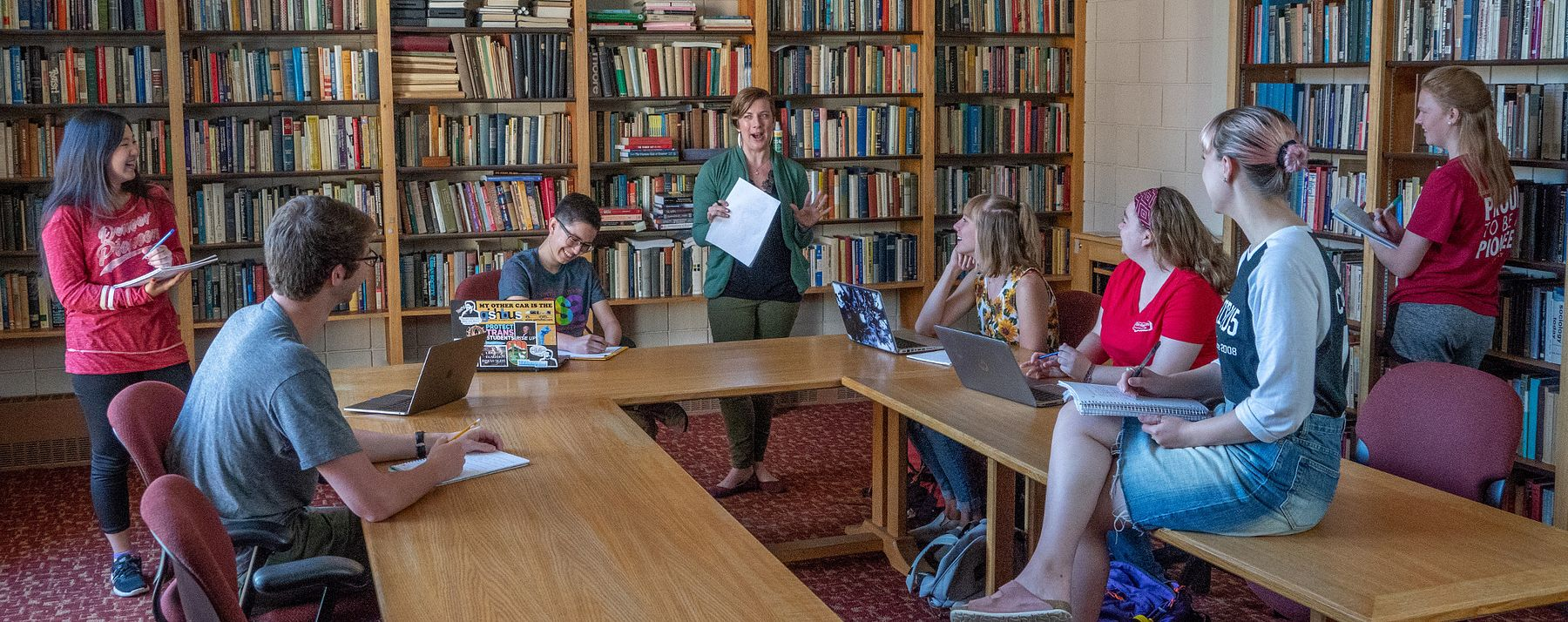 excited teacher talking to class in library