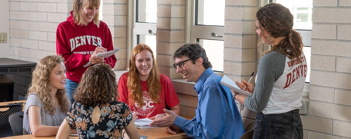 students and professor laughing together on DU campus