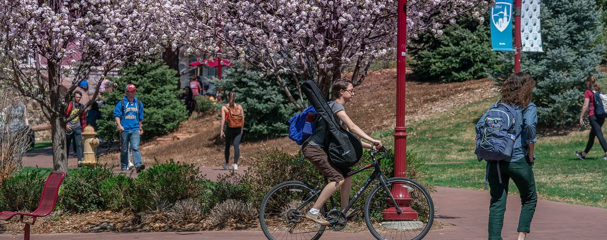 student on bike with walking students on campus outside