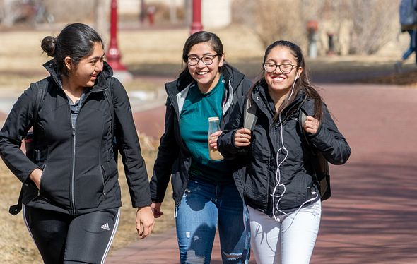 three women walking on campus and smiling