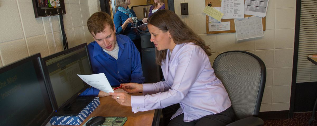 staff member looks over document with student in an office