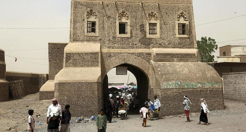 Yemenis walking through a gateway in the ancient city of Zabid, a UNESCO World Heritage Site. Retrieved from: the national.ae.