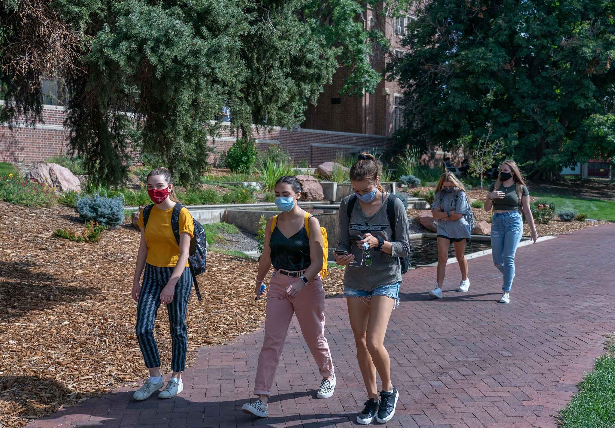students walking on campus while wearing masks