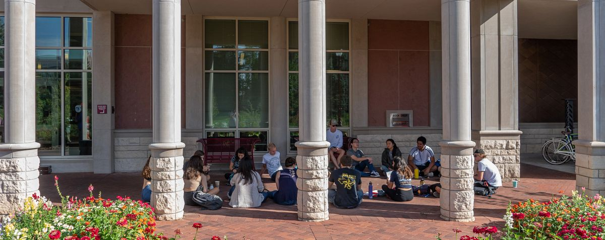 students sitting in front of library