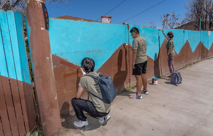 students repainting fence