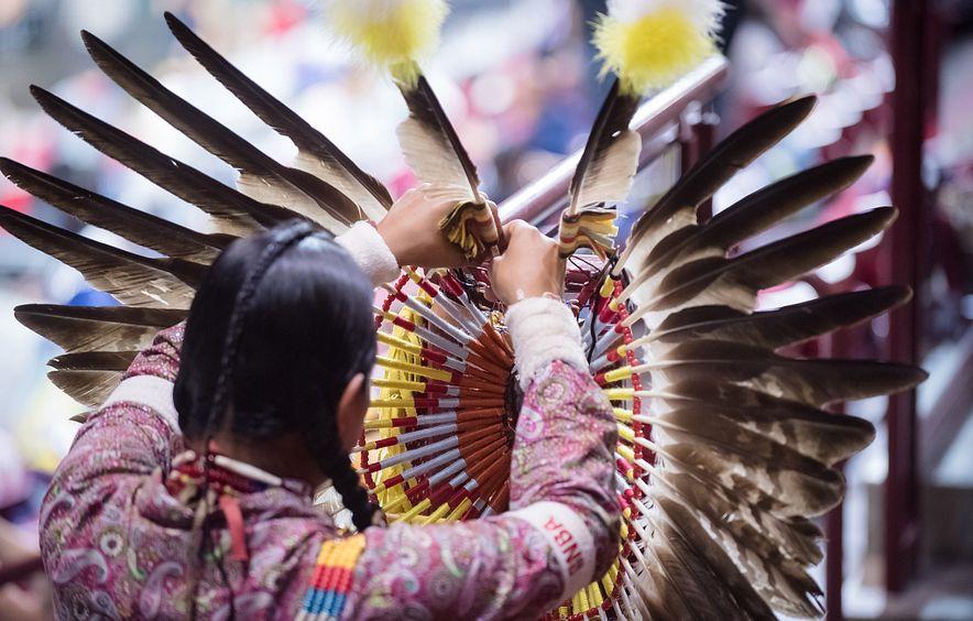 Pow wow participant adjusting a feather on regalia