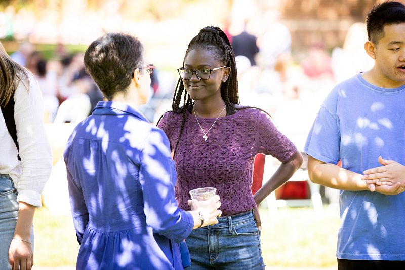 Faculty and student at a welcome event on the DU campus