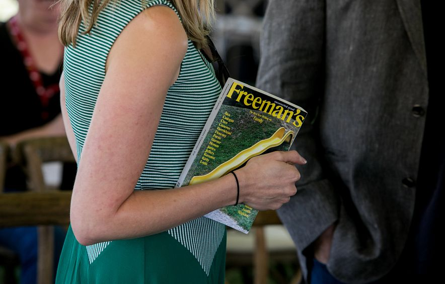woman holding copy of literary journal at DU poetry event