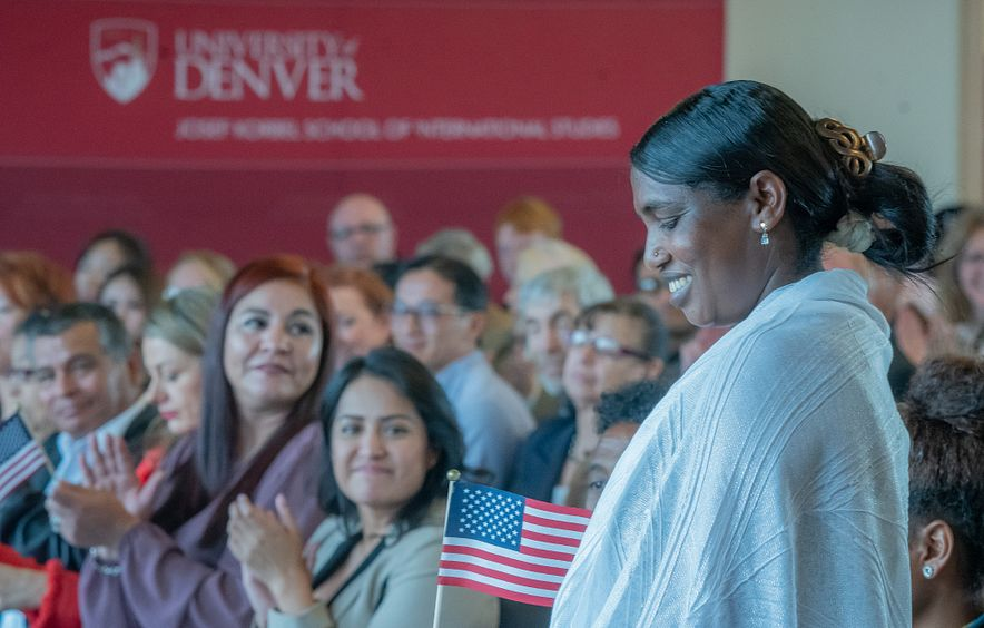woman standing with American flag at Naturalization Ceremony