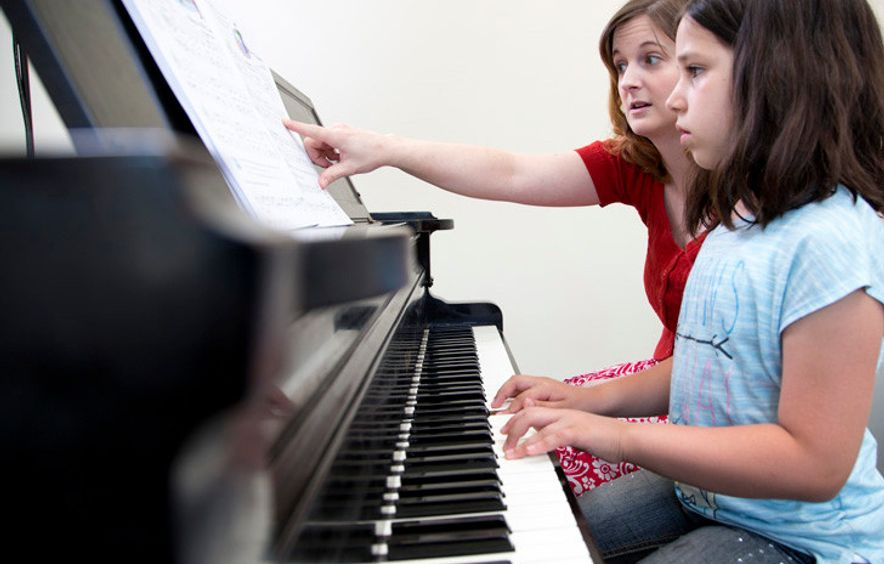 Student and teacher sit at the piano