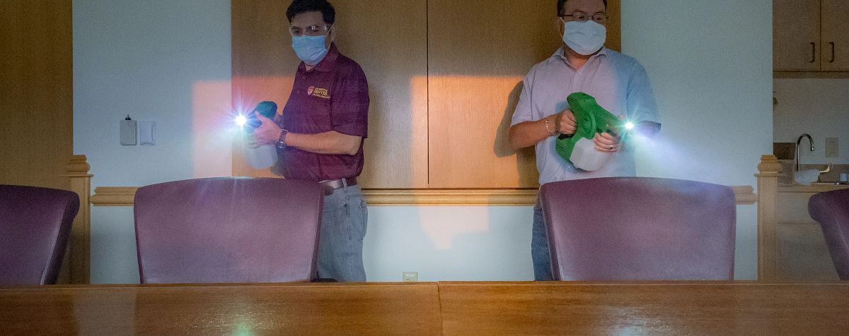 DU employees disinfect table on campus