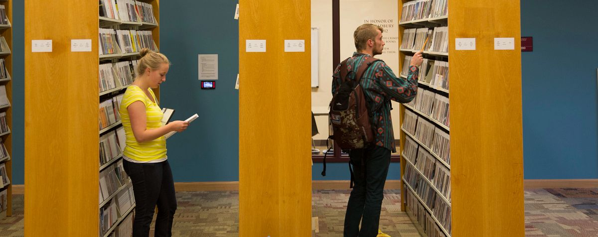 students looking through the library stacks