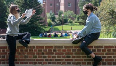 Two students wearing masks sit on campus to discuss a project