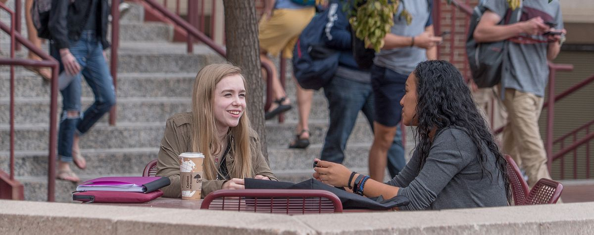 two girls talking and sitting at table outside Sturm Hall