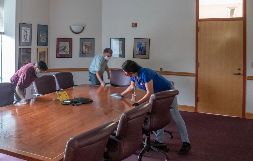 staff disinfecting table