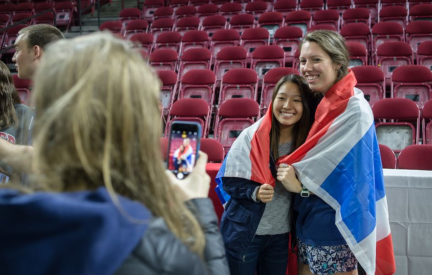 students wrapped in international flag smiling for photo