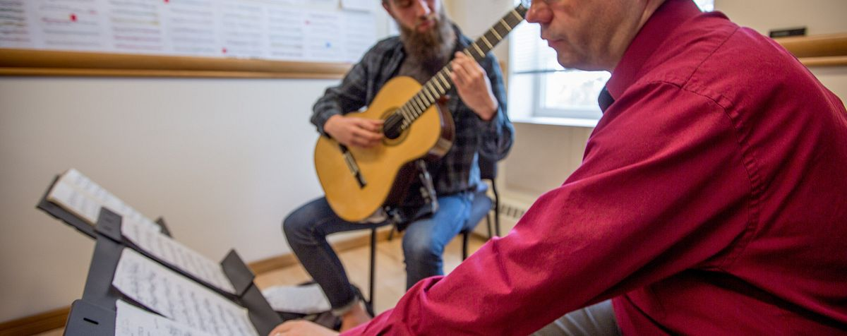 Guitarist works with his professor in studio lessons.