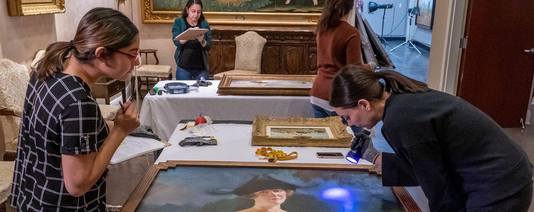 Students inspect fine artwork.