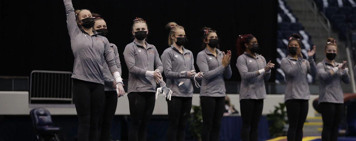 DU gymnastics team standing and wearing masks