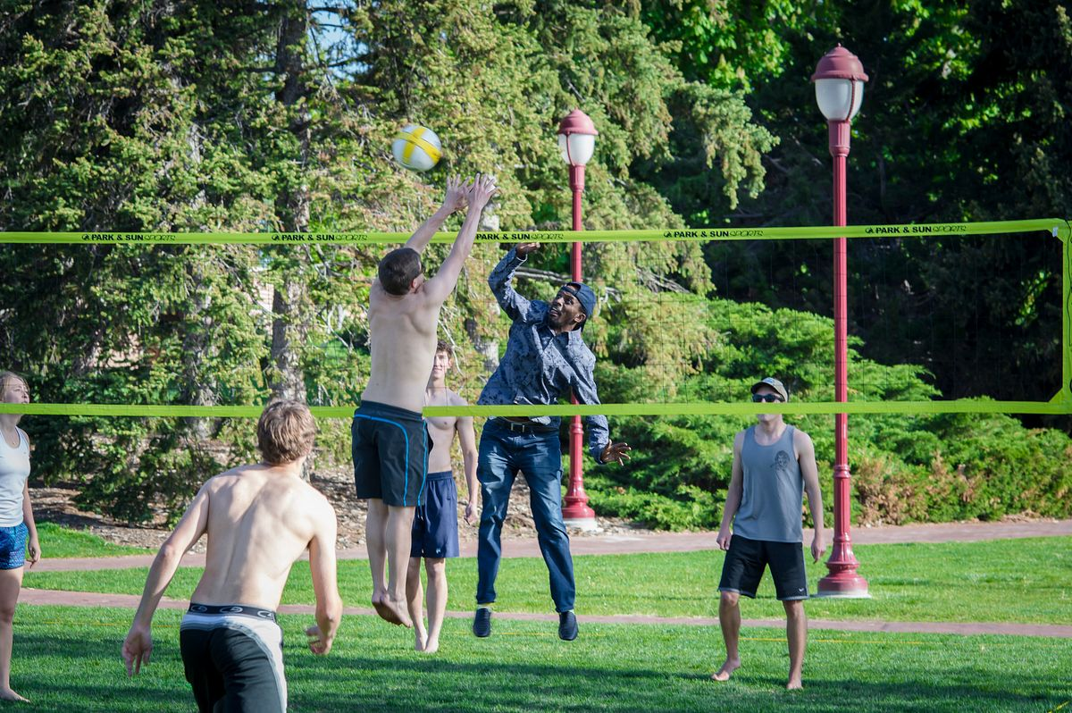 students leisurely playing volleyball on campus