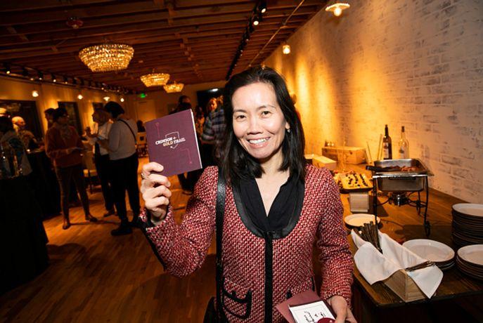 Alumni holding up the Crimson and Gold Passport