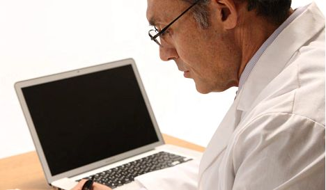 Man working with his laptop - Embase | Elsevier Solutions