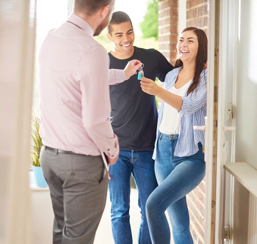Young couple recieving keys from agent