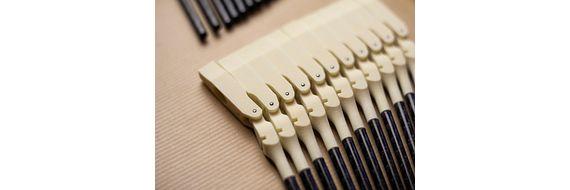 Kladívka vyrobená 3D tiskem v pianu. Velké piano se součástmi vyrobenými tiskem