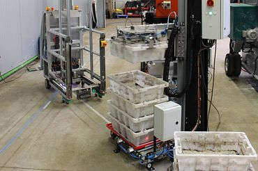 An automated guided vehicle system drives to the worm container removal station