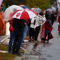 An IU umbrella shields a parade goer from the rain along Woodlawn Avenue during the IU Bloomington Homecoming Parade on Friday, Oct. 11, 2019.