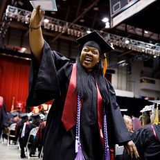 A graduate waves to friends in the audience during the IU Northwest Commencement at the Genesis Convention Center on Thursday, May 9, 2019.