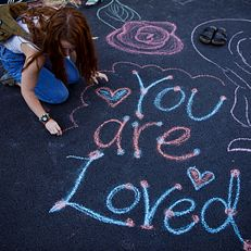 A student writes a message on the pavement using sidewalk chalk during the First Thursdays Festival on the Arts Plaza at IU Bloomington on Thursday, Sept. 5, 2019.