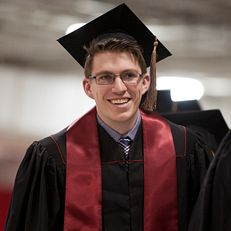 A graduate shares a smile as he waits to walk across stage to receive a diploma during IU Kokomo Commencement on Tuesday, May 12, 2015, at Ivy Tech in Kokomo.