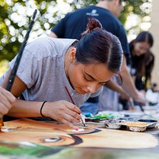 Indiana University junior Brianny Alvarado paints during the First Thursdays Festival on the Arts Plaza at IU Bloomington on Thursday, Sept. 5, 2019.