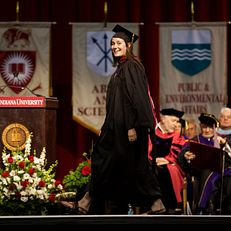 Graduate student Julia Rickles smiles to the crowd as she walks across the stage during the IU Graduate Commencement on Friday, May 8, 2015, in John Mellencamp Pavilion.