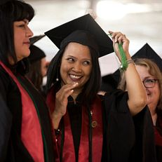 A graduate smiles as she moves the tassel on her mortarboard to the left during IU Kokomo Commencement on Tuesday, May 12, 2015, at Ivy Tech in Kokomo.