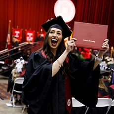 A graduate celebrates after receiving her diploma during the Indiana University Northwest Commencement at the Genesis Convention Center on Thursday, May 9, 2019.