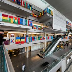 An IUPUI student inside the Campus Center with the international flags decorating the interior. Photo taken Monday, February 22, 2021 at IUPUI.