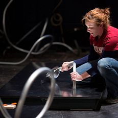Graduate student Bridgette Dreher attaches an electric light conduit and fixture to a board as she and fellow graduate students work to mock up the assembly of an art exhibit piece at the Wells-Metz Theatre on Thursday, Jan. 8, 2015. The piece will be part of the 2015 Prague Quadrennial of Performance Design and Space in June.